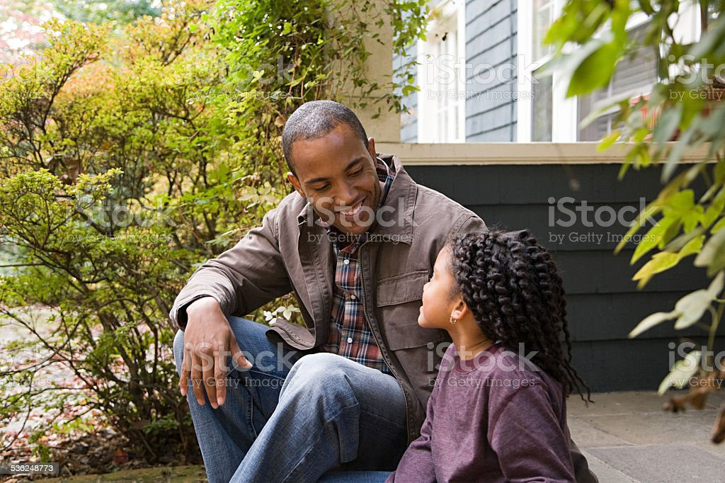 Father and daughter outside house stock photo