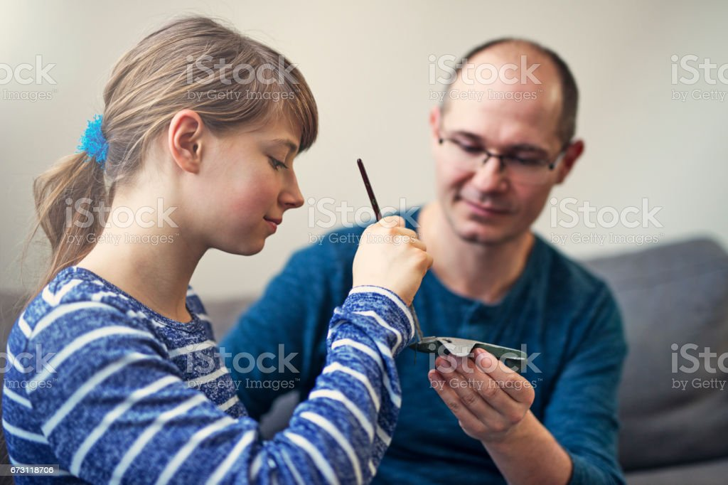Father and daughter painting toy plane model together stock photo
