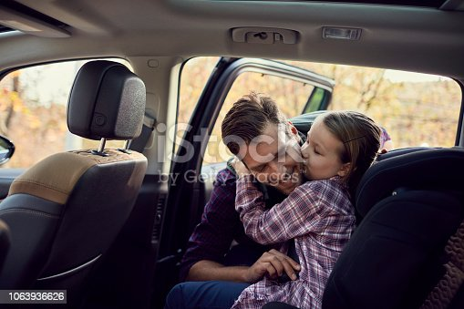Close up of a father helping his daughter strap her seatbelt
