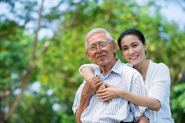 Father and daughter Portrait of smiling Vietnamese woman hugging her father vietnamese ethnicity stock pictures, royalty-free photos & images