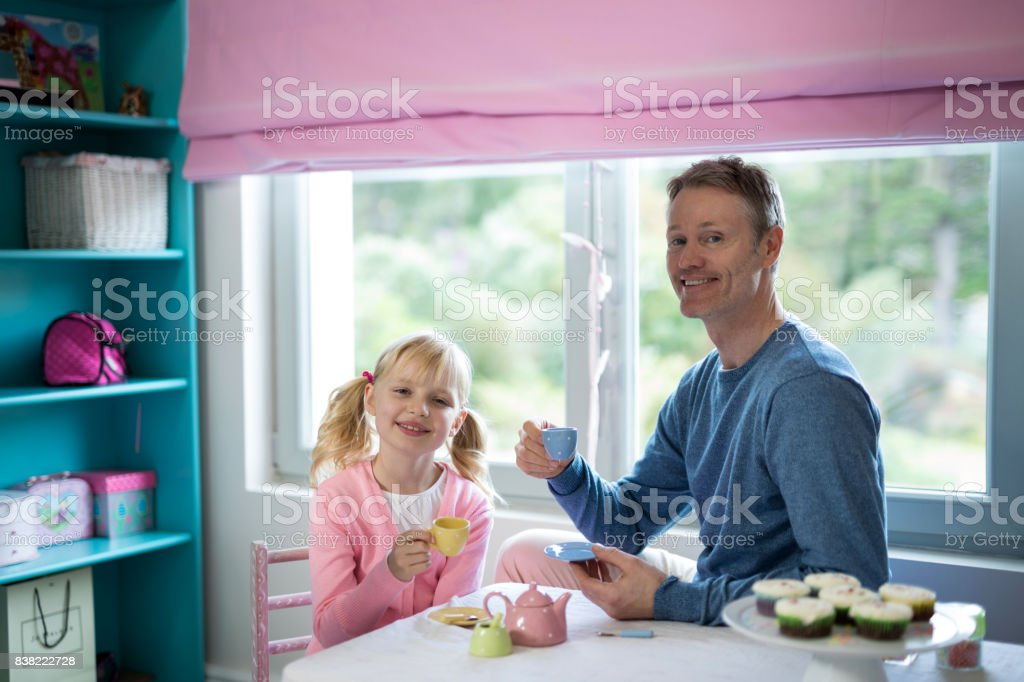 Father and daughter playing a tea set role play stock photo