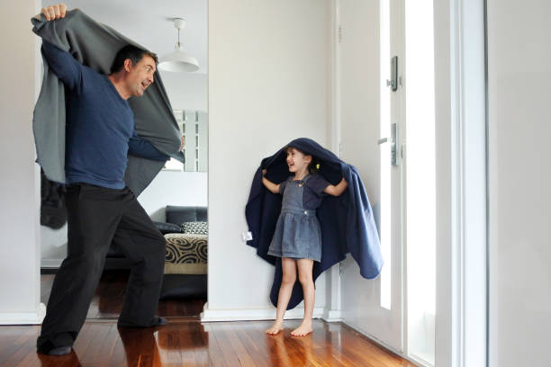 Father and daughter playing around the house while forced to stay at home because government policies efforts to prevent pandemic coronavirus (COVID-19) spreading stock photo
