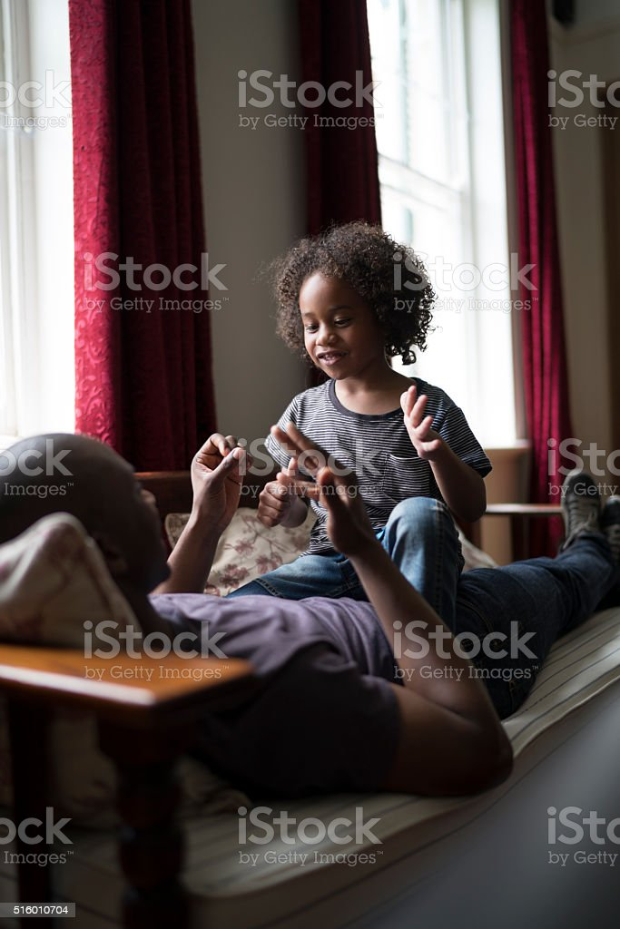 Father and daughter playing counting game at home stock photo