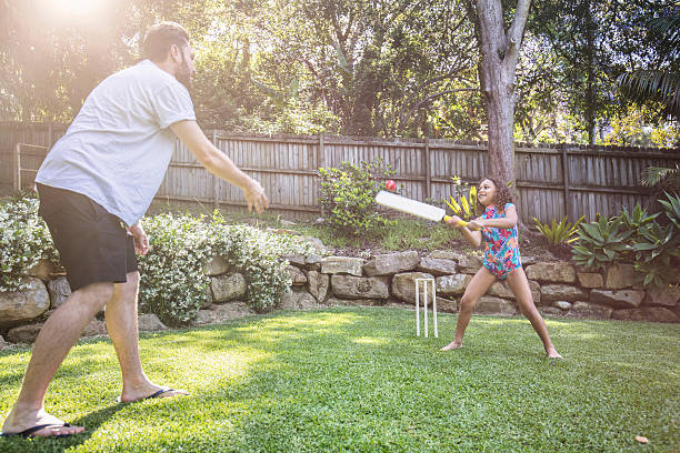 Father and daughter playing cricket in the garden Aboriginal father and daughter playing cricket in the garden, father is throwing the ball to her and she is having a great time hitting it. sport of cricket stock pictures, royalty-free photos & images