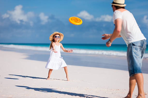 Father and daughter playing frisbee Father and daughter playing frisbee at beach plastic disc stock pictures, royalty-free photos & images