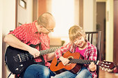 istock Father and daughter playing guitars together 159179254