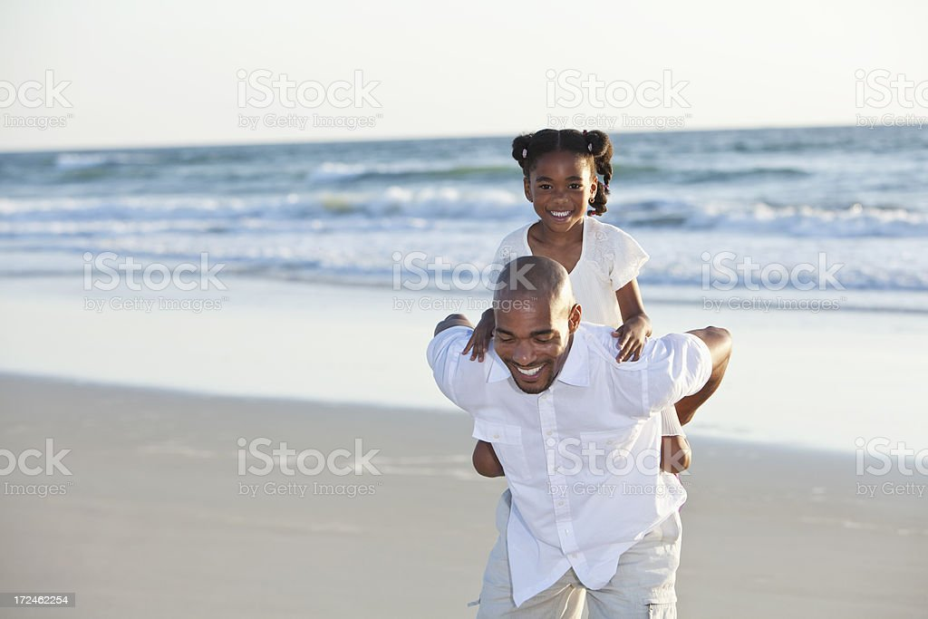 Father and daughter playing on beach stock photo