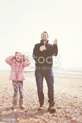 453383283 istock photo Father and Daughter Playing on Beach with Kite 187051890