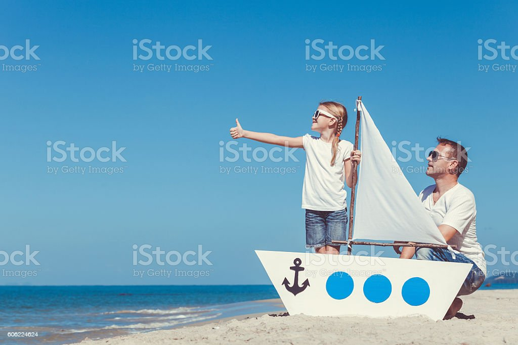 Father and daughter playing on the beach at the day. - foto stock