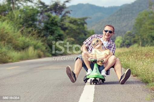 586180632istockphoto Father and daughter playing on the road. 586184354