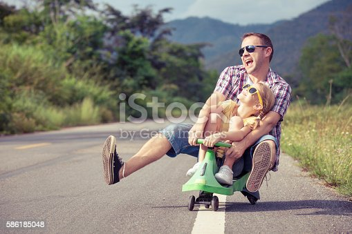 586180632istockphoto Father and daughter playing on the road. 586185048