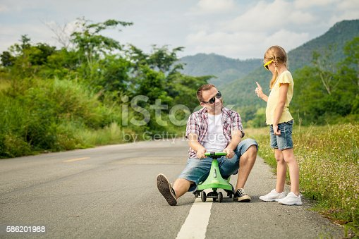 586180632istockphoto Father and daughter playing on the road. 586201988