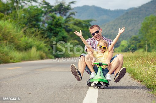 586180632istockphoto Father and daughter playing on the road. 586203016