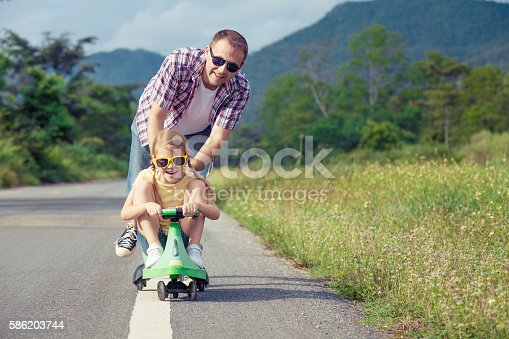 586180632istockphoto Father and daughter playing on the road. 586203744