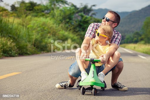 586180632istockphoto Father and daughter playing on the road. 586204718