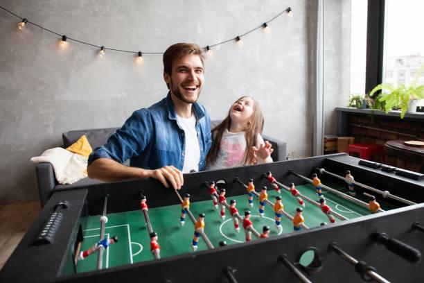 Vater und Tochter spielen zu Hause Tischfußball – Foto