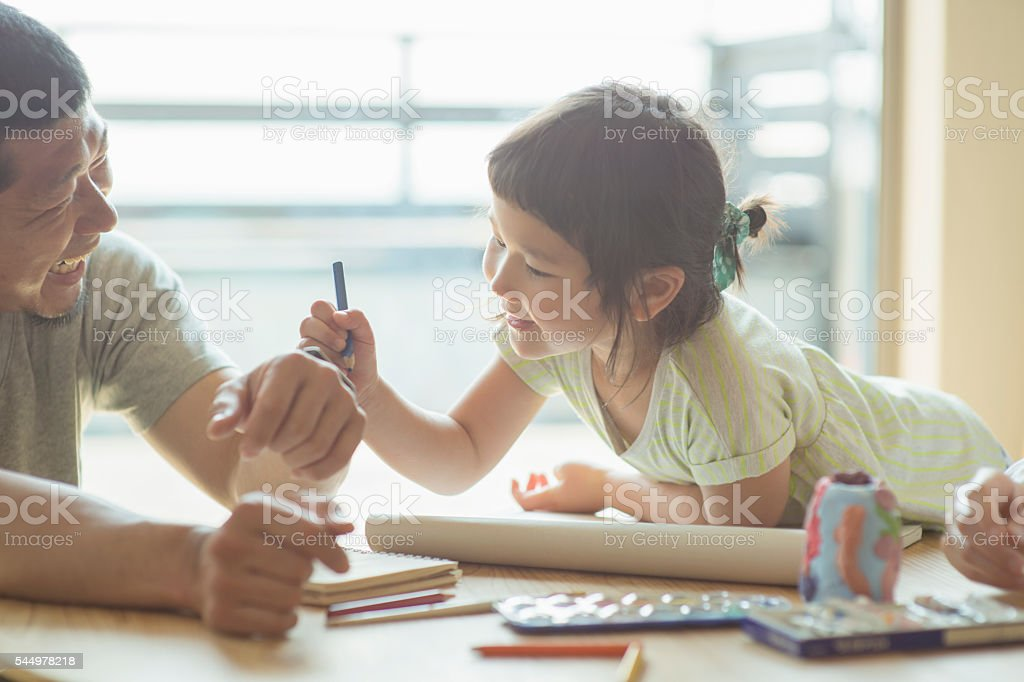 Father and daughter playing together at home stock photo