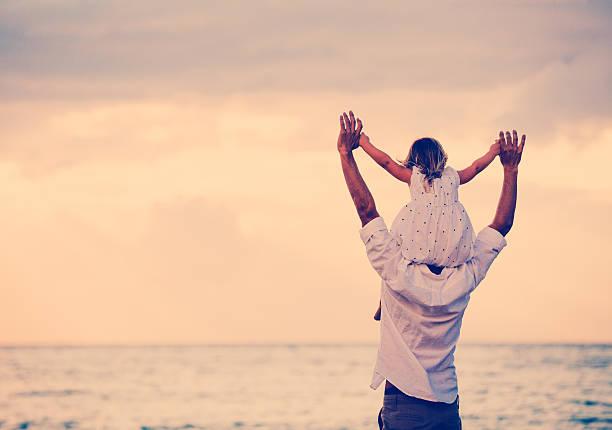 Vater und Tochter spielen am Strand bei Sonnenuntergang – Foto
