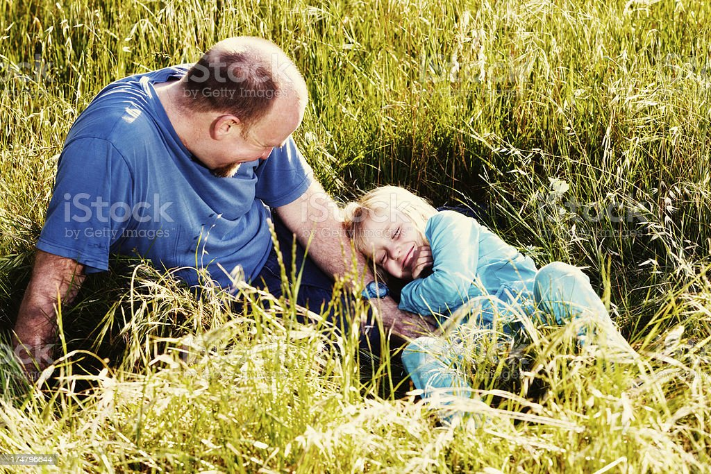 Father and daughter playing together, laughing in long grass stock photo