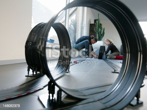 496487362istockphoto father and daughter playing with a race circuit 145052373