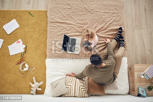 994789938 istock photo Father and Daughter Playing with Laptop Top View 1191693335