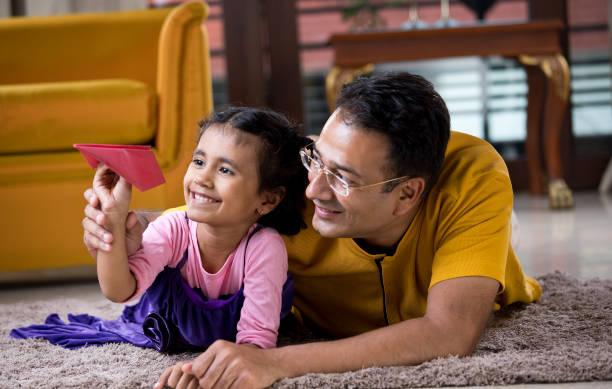 Vater und Tochter spielen mit Papierflugzeug – Foto