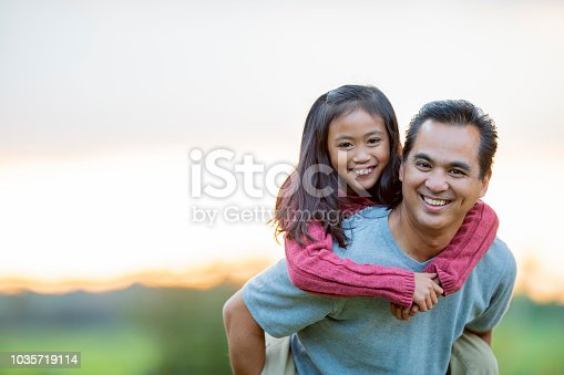 An asian elementary aged girl and holds onto her fathers back and smiles at the camera. Her father his smiling genuinely as he holds his daughter on his back.