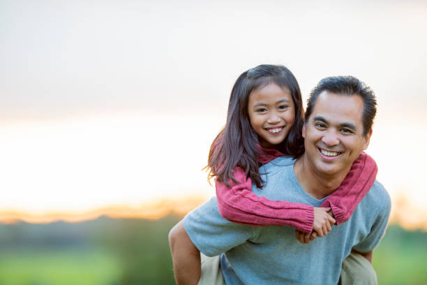Father and daughter portrait outside in the summertime An asian elementary aged girl and holds onto her fathers back and smiles at the camera. Her father his smiling genuinely as he holds his daughter on his back. filipino ethnicity stock pictures, royalty-free photos & images