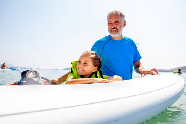 Father and Daughter Portrait while Teaching her to Windsurf - Stock Photo Father and Daughter Portrait while Teaching her to Windsurf - Stock Photo wet clothing women t shirt stock pictures, royalty-free photos & images