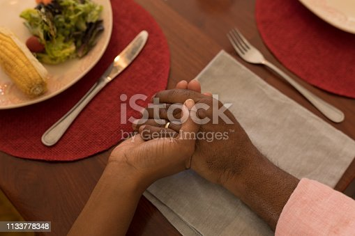 Close-up of  African American father and daughter holding each other hand and praying before having meal on dining table at home