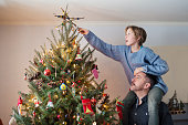 Father and teenage daughter putting the finishing touch on their decorated Christmas tree at home.  Daughter is on dad shoulders to be tall enough to put the homemade star on top of the tree. Horizontal indoors mid length shot with copy space. This was taken in Quebec, Canada. Note to inspector: Art on wall was completely modified on Photoshop.