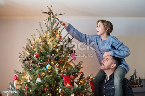 istock Father and daughter putting the finishing touch on Christmas tree at home. 852696242