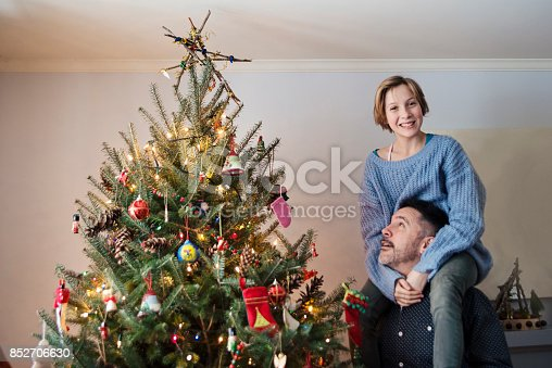 istock Father and daughter putting the finishing touch on Christmas tree at home. 852706630