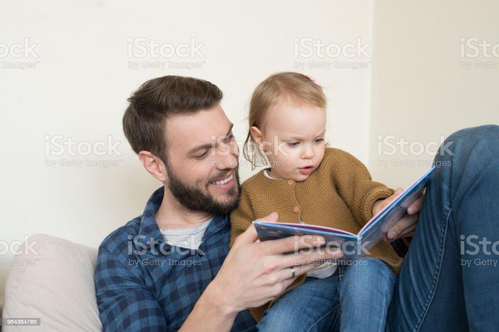 Pai e filha lendo um livro - Foto de stock de Adulto royalty-free