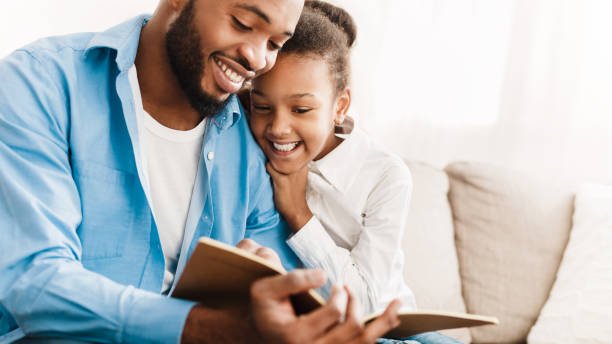 Father and daughter reading book together at home Father and daughter reading book together, sitting on sofa at home one parent stock pictures, royalty-free photos & images
