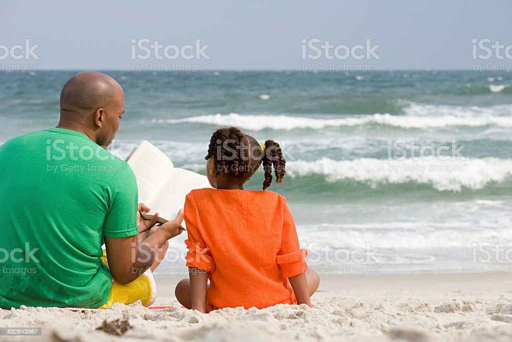 Father and daughter reading stock photo