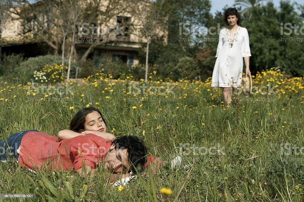 Father and daughter (8-9) relaxing on meadow, mother in background royalty free stockfoto
