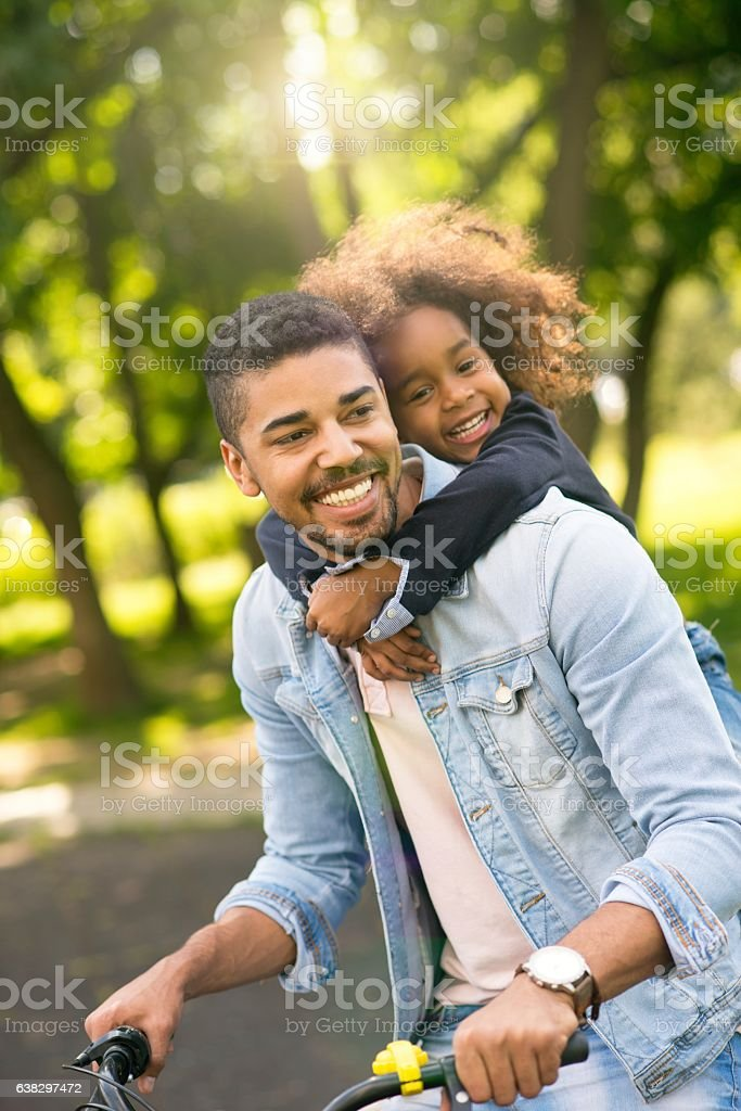 Father and daughter riding a bike together. stock photo
