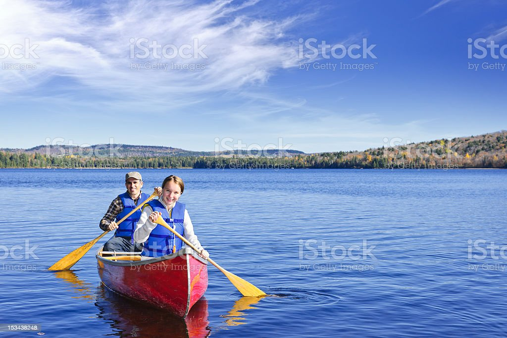 Father and daughter rowing a canoe on a calm lake stock photo