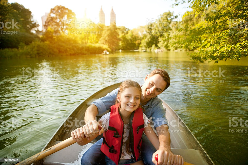 Father and daughter rowing boat stock photo
