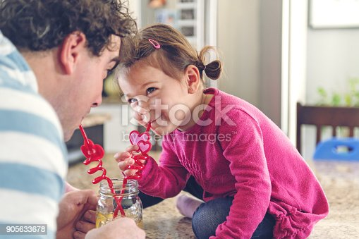 istock Father and daughter sharing a lemonade 905633678