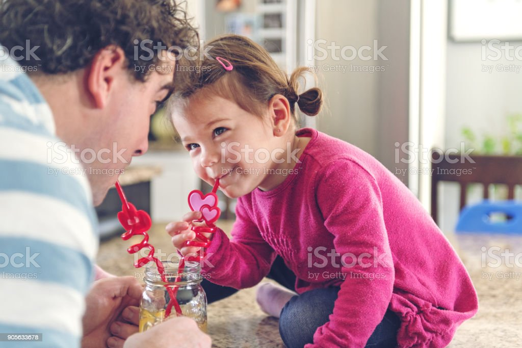 Father and daughter sharing a lemonade stock photo