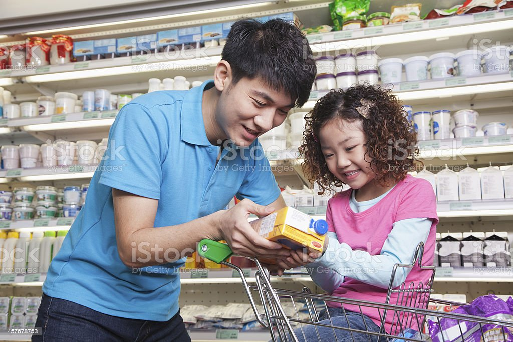 Father and Daughter Shopping in Supermarket, Looking at Juice Box stock photo