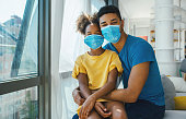 Closeup front view of a mid 30's african american man with his daughter staying at home during coronavirus pandemic. They are staying at home, wearing face masks and looking at the camera.
