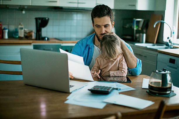 Father and daughter sitting in the kitchen Photo of a father and daughter sitting in the kitchen,daughter is playing while dad is sitting worried and checking his bills genderblend stock pictures, royalty-free photos & images