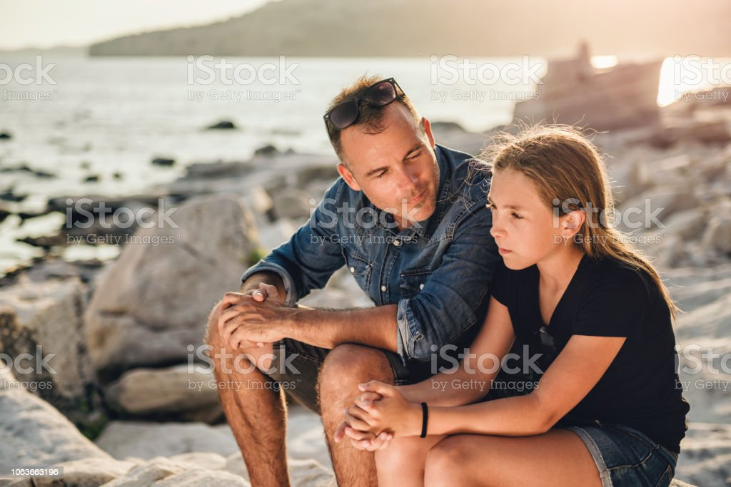 Father and daughter sitting on a rocky beach and talking stock photo