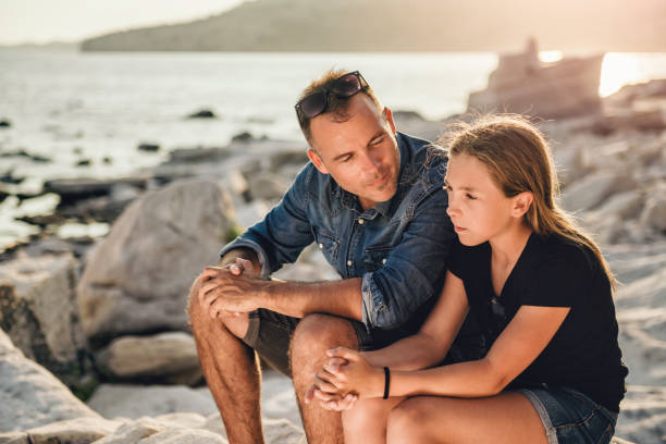 Father and daughter sitting on a rocky beach and talking Father and daughter relaxing on a rocky beach by the sea and having time together parent stock pictures, royalty-free photos & images