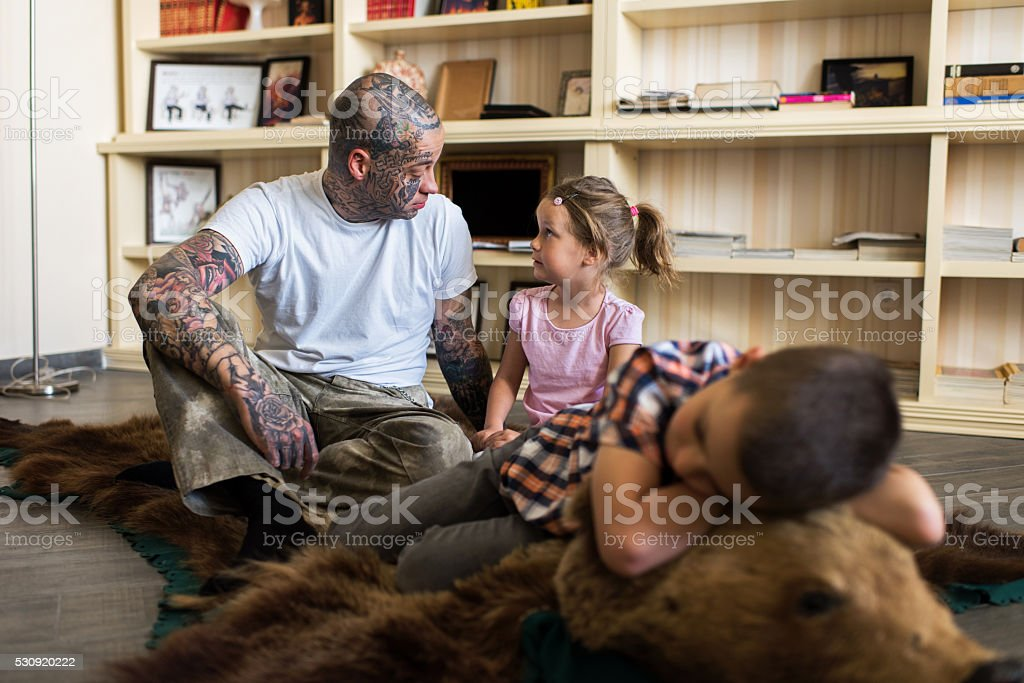 Father and daughter sitting on bear skin rug and communicating. stock photo