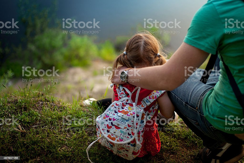 father and daughter sitting on the Bank of the river stock photo