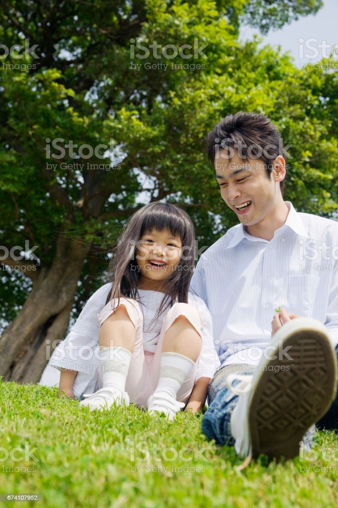 Father and daughter sitting on the grass in the Park stock photo